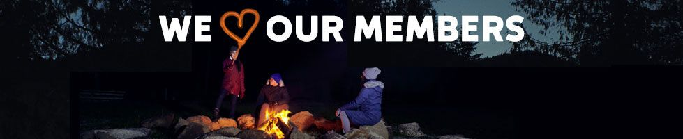 People sitting around a campfire, We Heart Our Members.