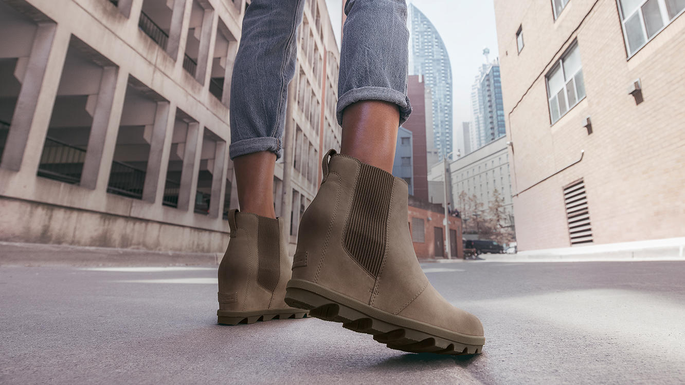 Close-up of woman's legs wearing JOA Wedge Chelsea boots in an urban setting