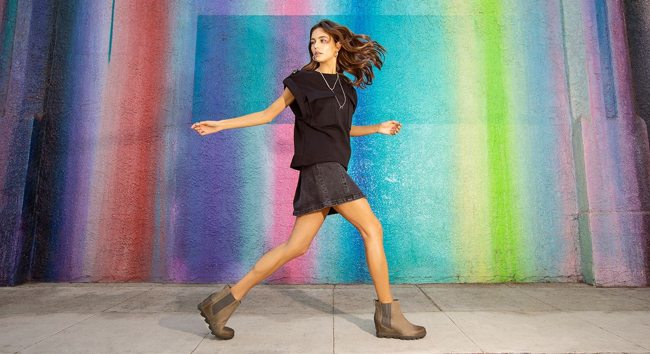 fa53af84922 Woman wearing Joan Wedge Chelsea boots while walking though a colorful city  setting. SPRING 2019