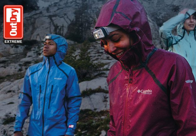 A man and a woman wearing a rain jackets in the rain. OutDry Extreme logo.
