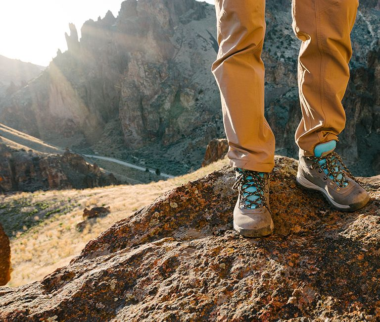c550bda98c8 Hikers standing on rocky peak in hiking boots.