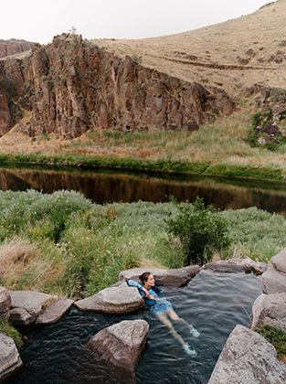 Woman soaking in a hot spring in a desert-like area.