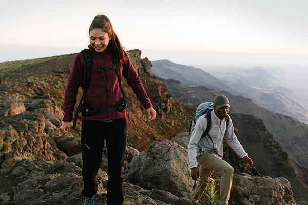 A woman and man hiking in the mountains.
