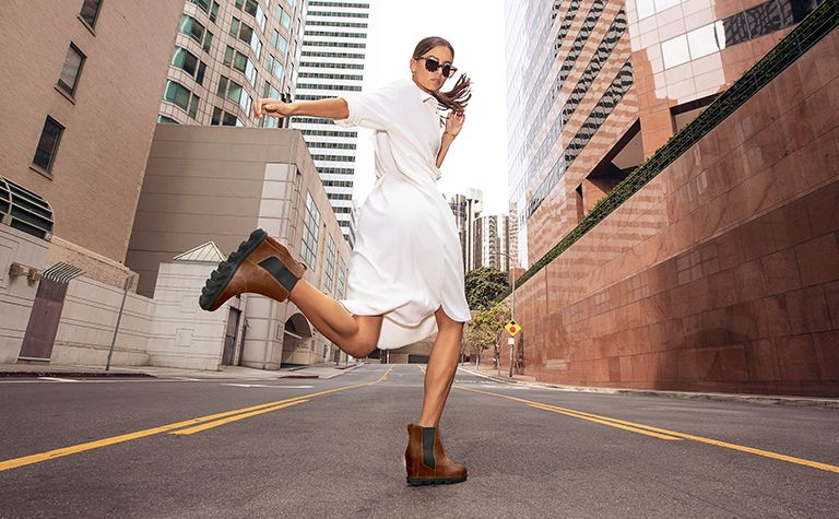 A woman walking through the city in Joan Wedge Chelsea boots