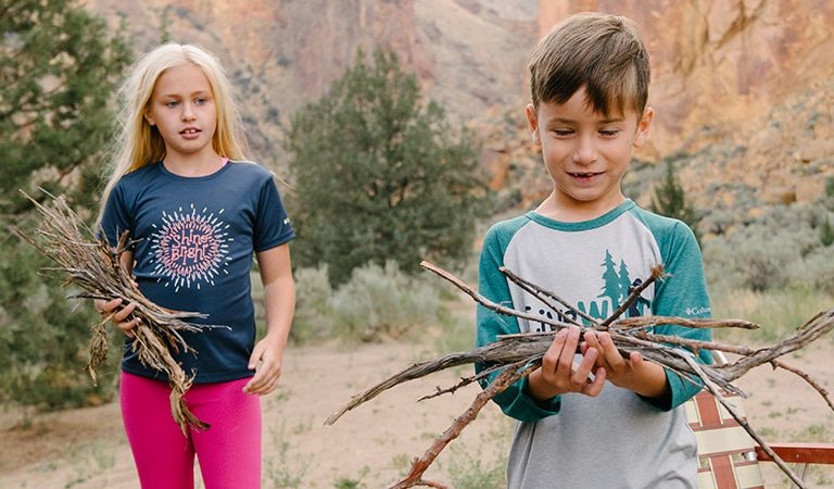 A boy and girl in graphic t-shirts gathering sticks at a campsite.