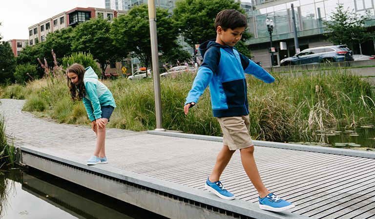 A boy and girl walking on a path over water in the city.