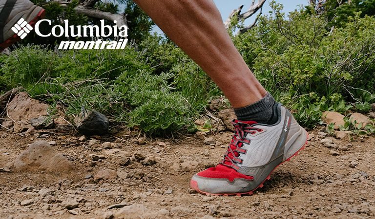 Close-up of someones feet running on a trail.