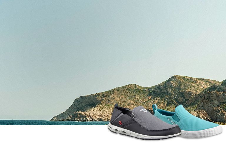 7970eb2fbfba5 Two slip-on PFG shoes in front of an an ocean shoreline background.
