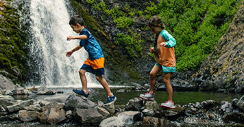 Kids hiking near a stream.
