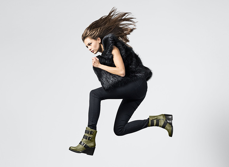 Woman jumping in boots.