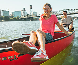 A woman in a canoe wearing Columbia shoes