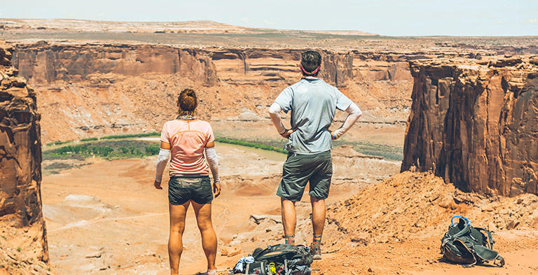 A man and woman stand overlooking the White Rim Trail.