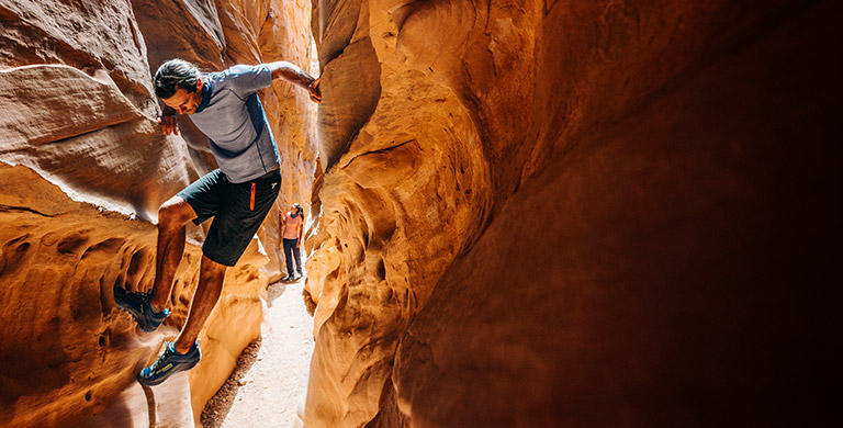 A man and woman in Titanium gear navigate a narrow slot canyon.