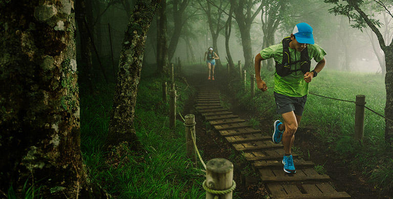 A man and woman run up a misty mountain trail.