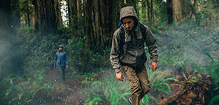 A man and woman hike in a rainy forest wearing Columbia gear.