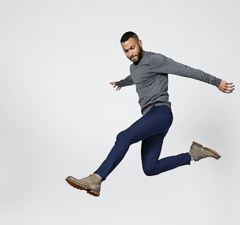A young man leaping through the air wearing boots.
