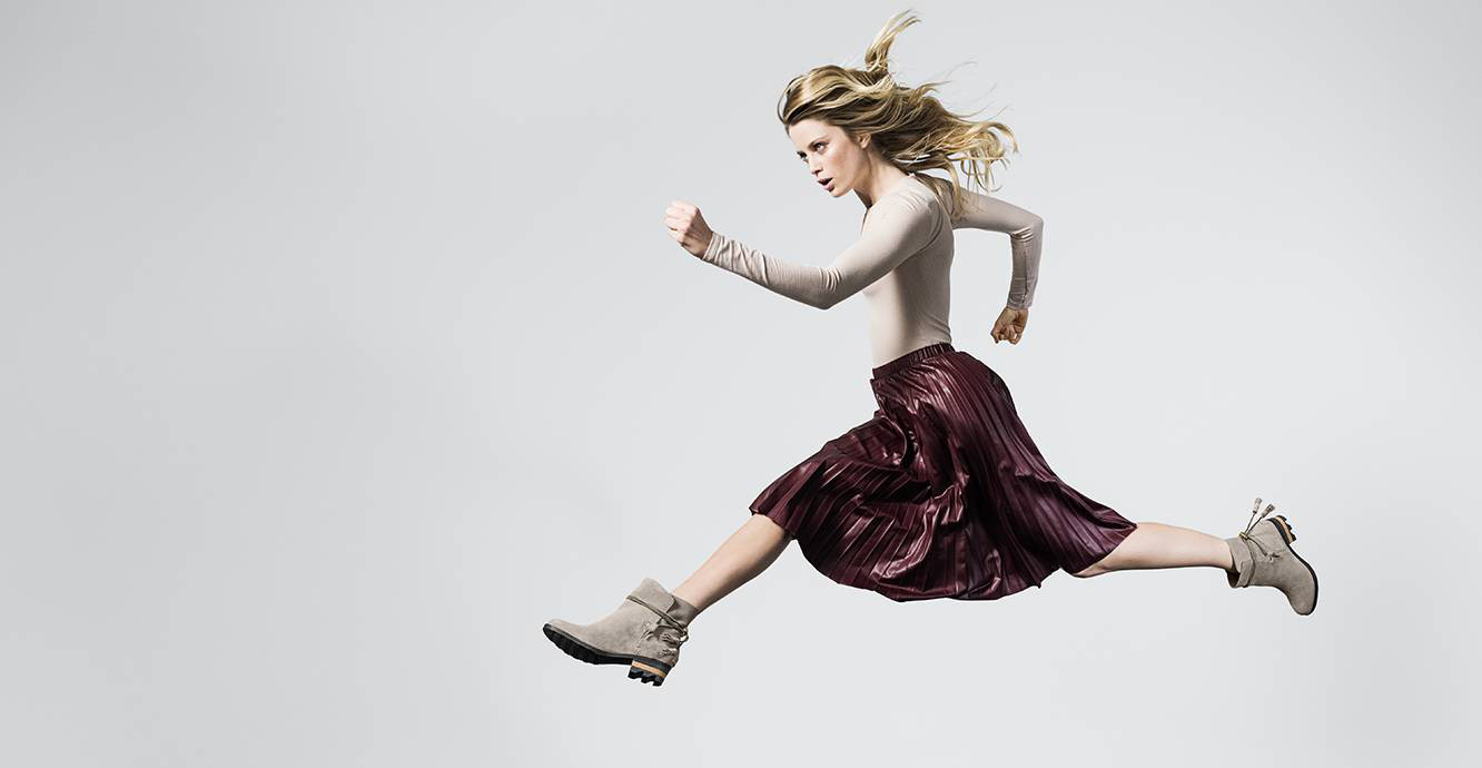 A woman jumping in a dress and boots.