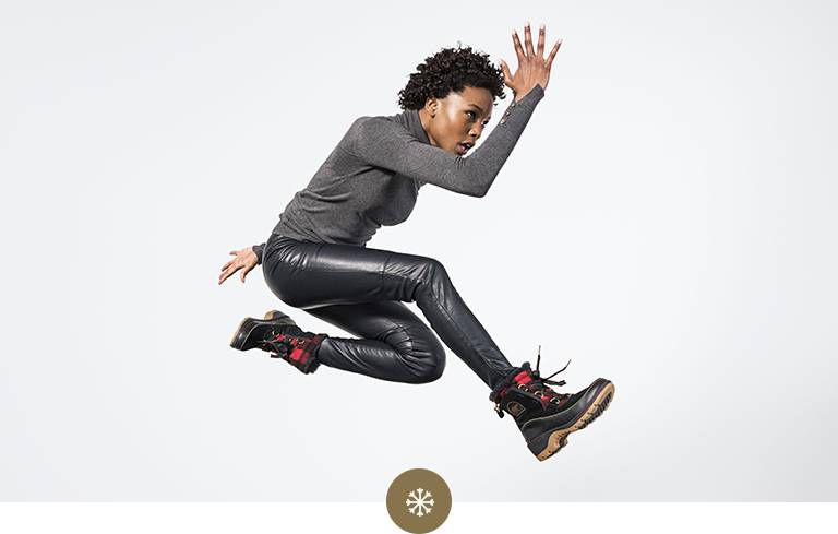 Woman jumping in snow boots.
