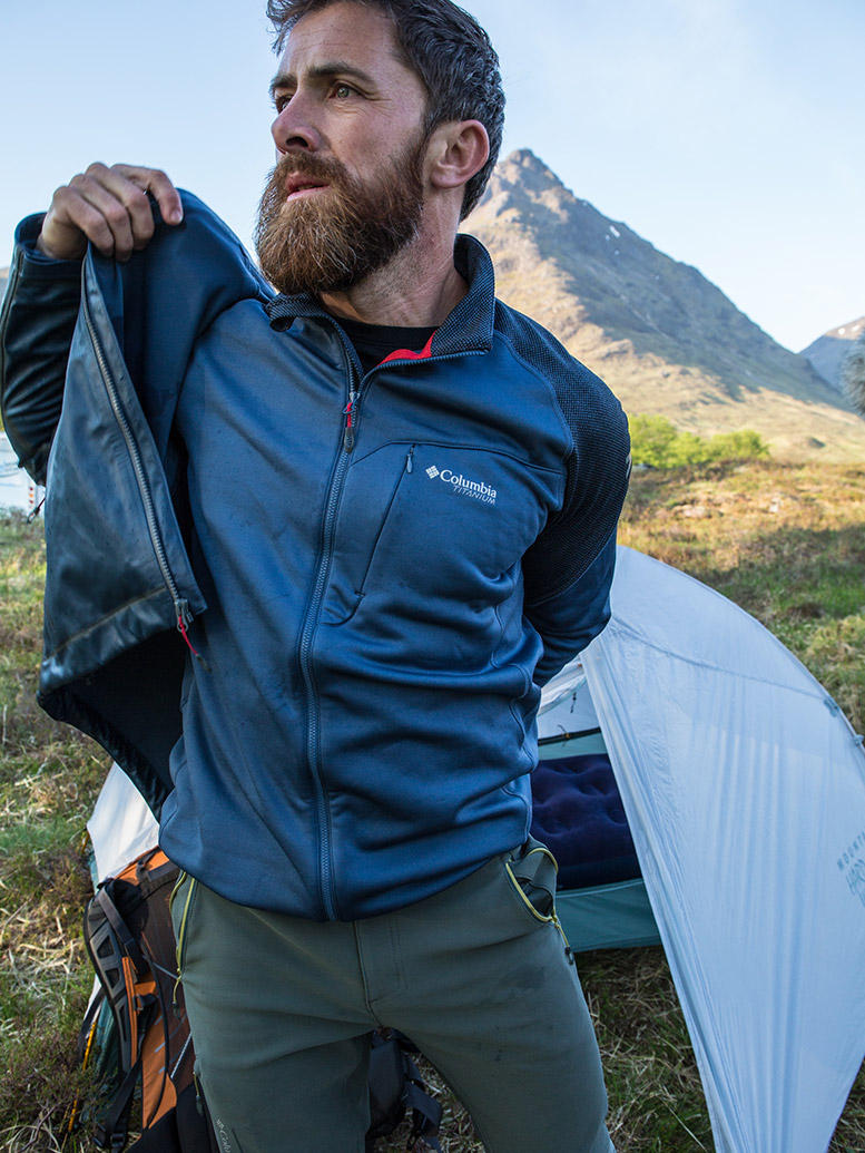 Aldo Kane in Columbia gear emerging from his tent while hiking the West Highland Way in Scotland.