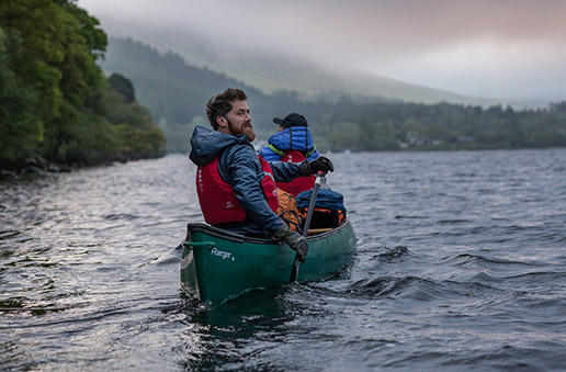 Aldo Kane and Mamrie Hart paddling a canoe on Loch Lomond in Scotland.