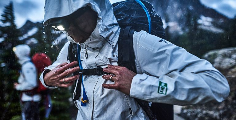 A person wearing an OutDry Extreme Eco jacket in a rainstorm.