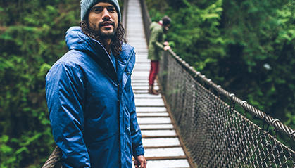 A man in outdoor casual gear on a suspension bridge in the forest.
