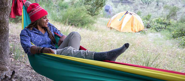Columbia Director of Toughness Faith Briggs relaxes in a campsite hammock.