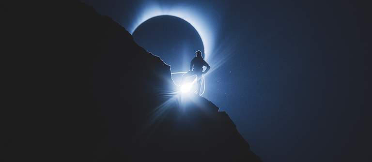 "Still frame of a climber in front of a total solar eclipse; ""Totality"" video."