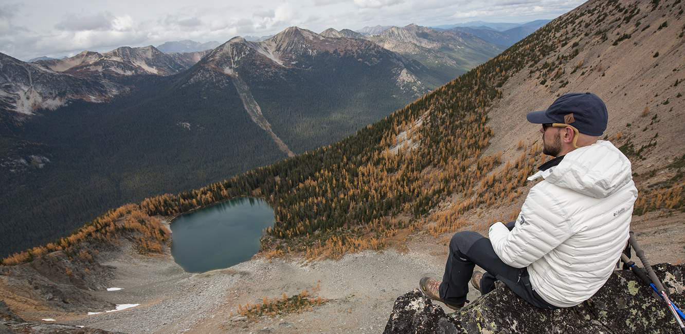 A man in a white OutDry Ex Eco Down Jacket sits on a rock looking down at a mountain valley and lake below him.