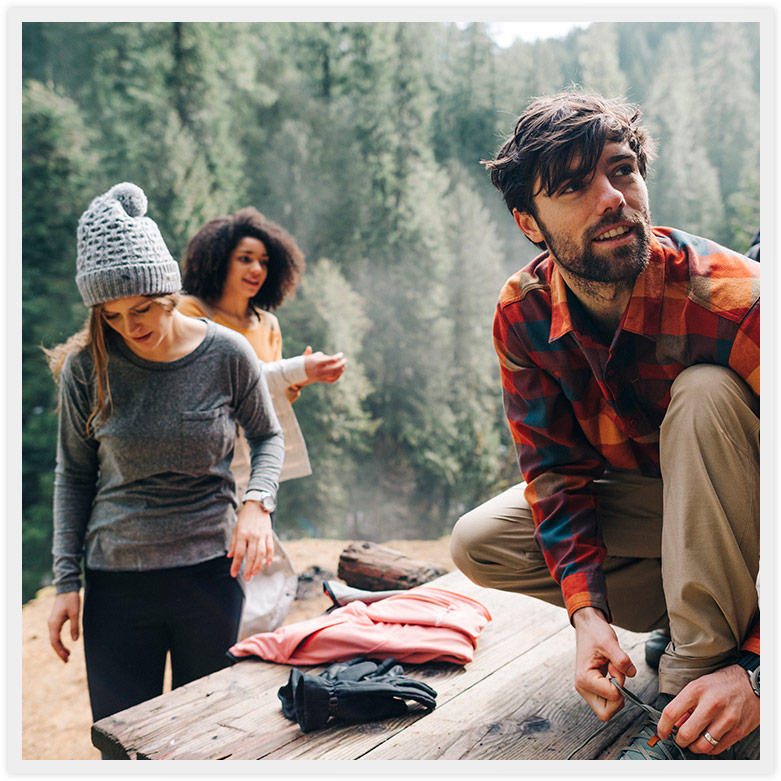 A group of young people in outdoor casual wear gather in a forested setting.
