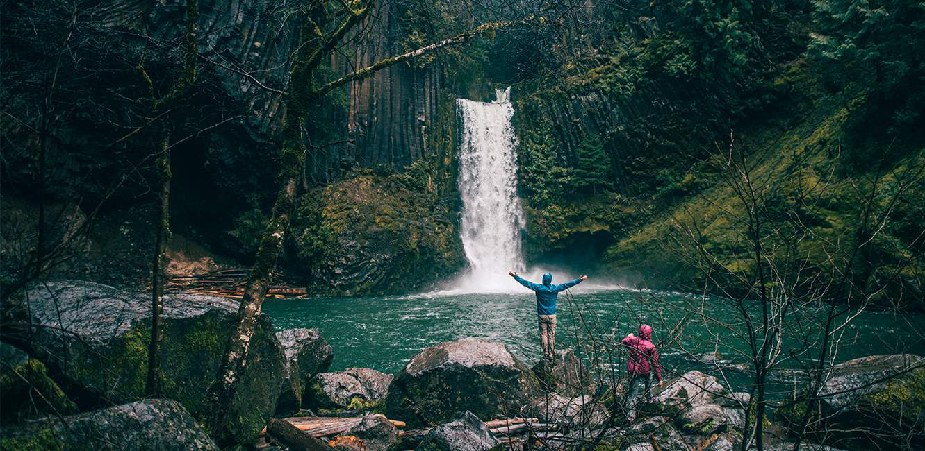 Two hikers stand before a majestic waterfall in a damp forest.