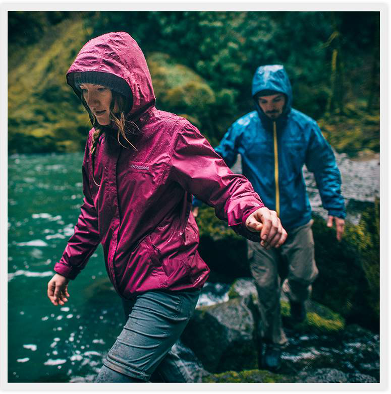 A woman and man in rainwear step over rocks beside a river or lake in the forest.