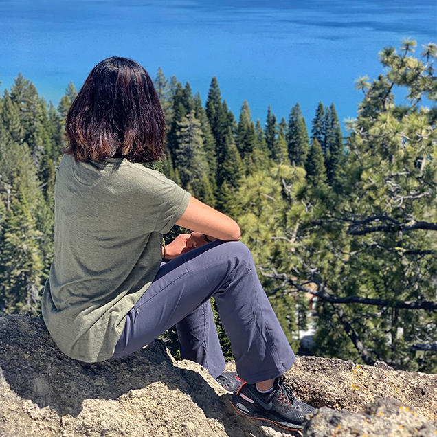 A woman wearing Stretch Zion pants sits on a cliff overlooking a forest and lake.