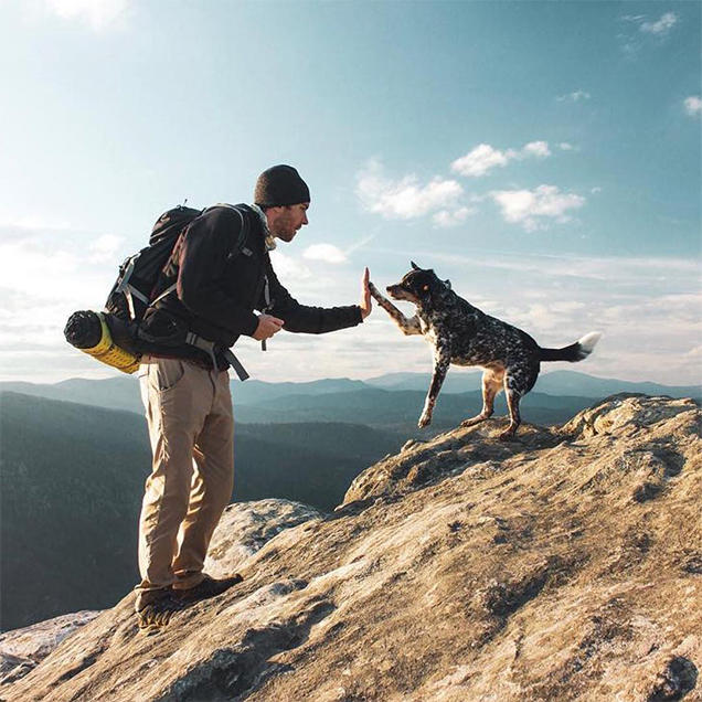 A man wearing a backpack and Stretch Zion pants high fives his dog while on a hike in the mountains.