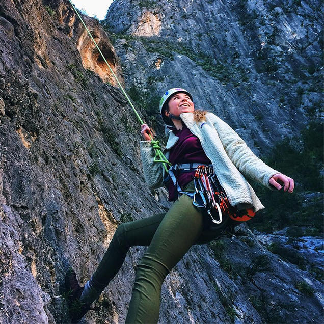 A woman wearing green Stretch Zion pants repels down the side of a cliff.