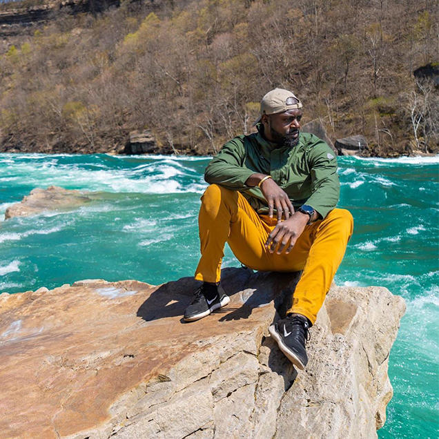 A man wearing yellow Stretch Zion pants and a green jacket sits on a rock near vivid blue water.