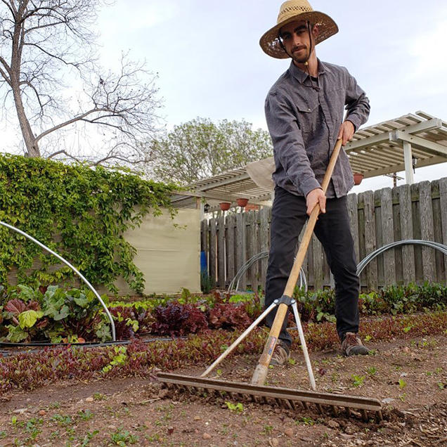 A man wearing Stretch Zion pants and a sun hat uses a large rake to work the land.