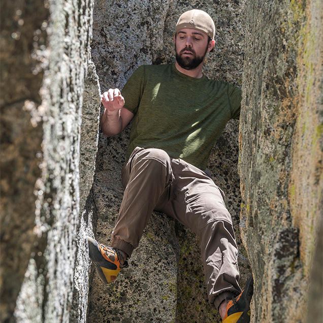 A man wearing Stretch Zion pants climbs between two boulders.