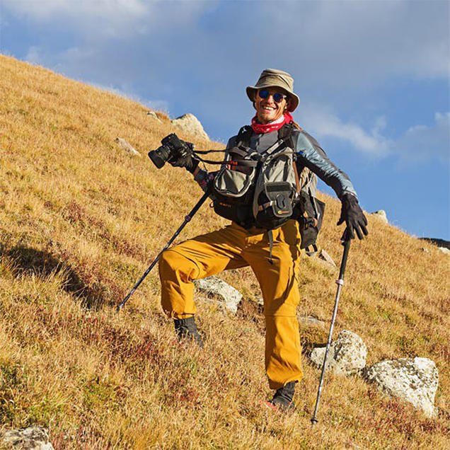 A man wearing yellow Stretch Zion pants and loaded with photography gear hikes up a grassy hill.