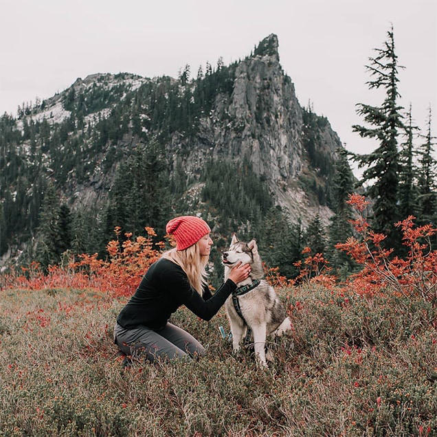 A woman wearing Stretch Zion pants pets her husky dog surrounded by red flowers.