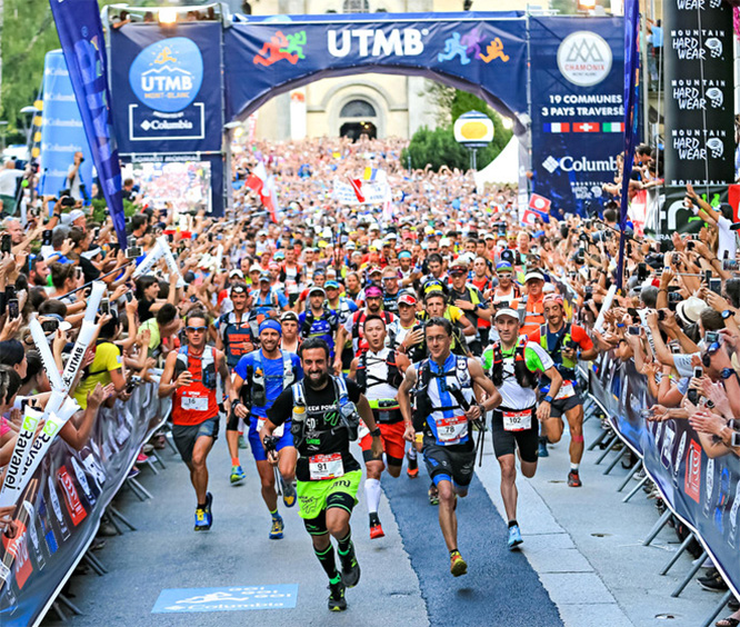 Runners sprint away from the UTMB starting line.