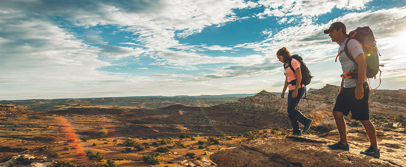 Two hikers jumping on a rocky outcrop. See our Hiking Guide.
