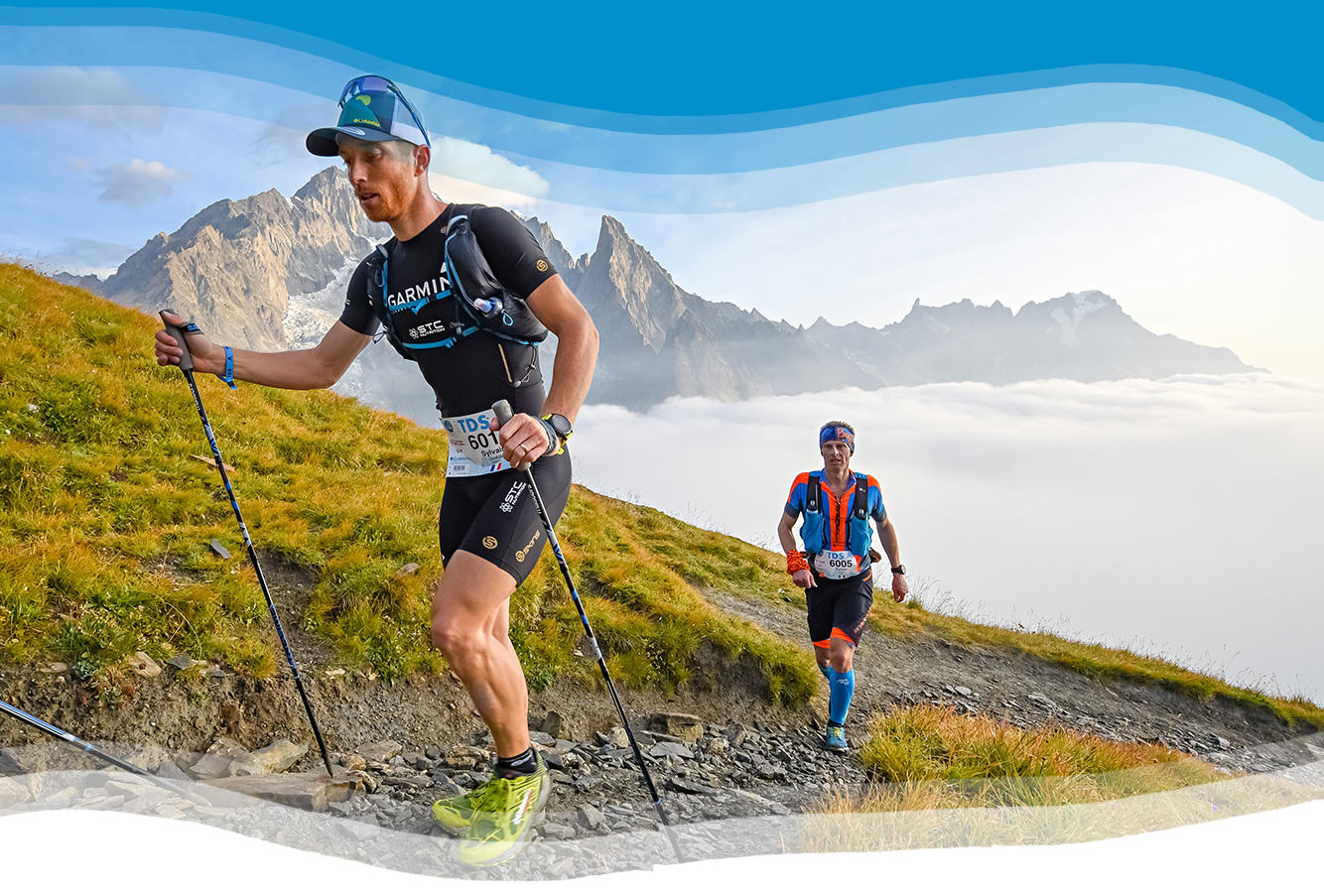 Video still of two UTMB participants on a mountain trail.