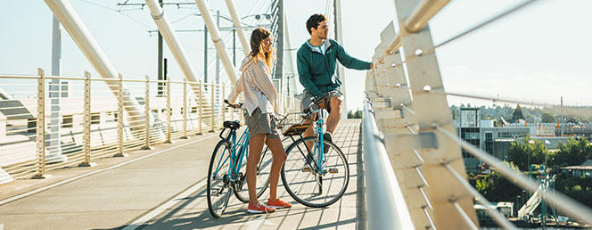 A woman and a man with bicycles on a bridge
