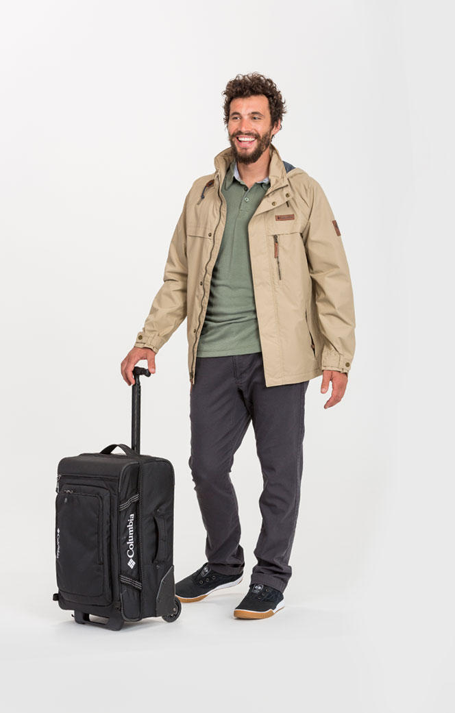 A man wearing a beige jacket and holding a roller bag