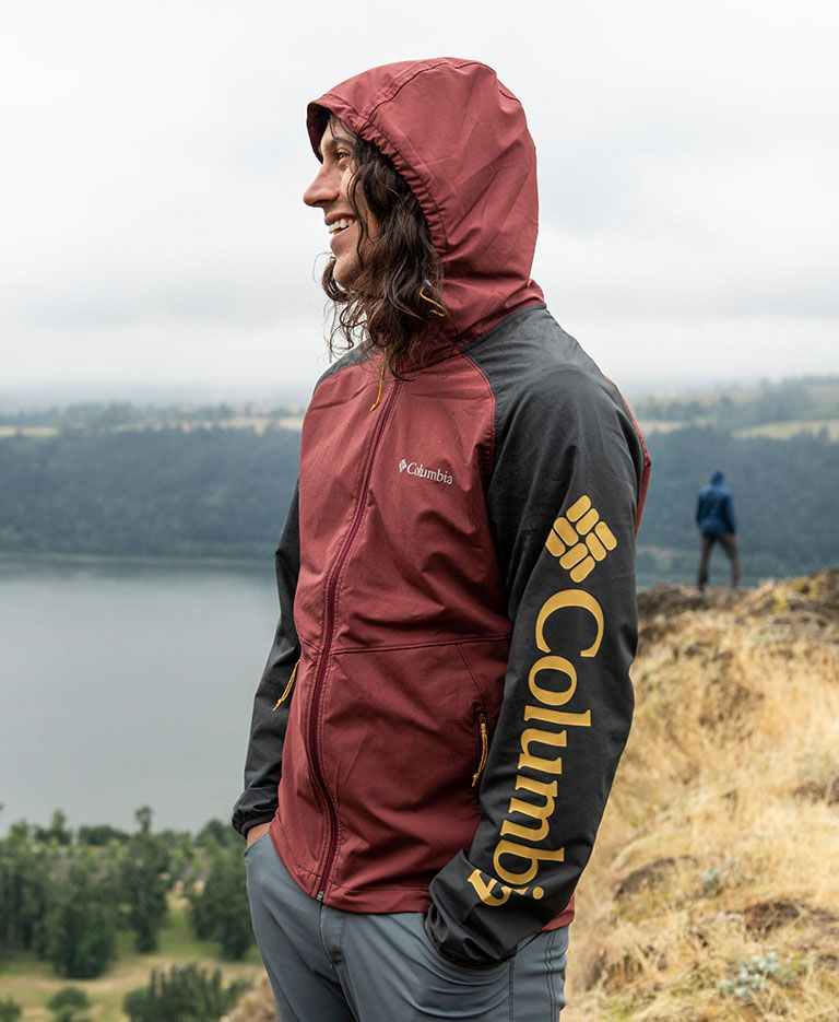 A person hiking in a blue Columbia casual rain jacket.