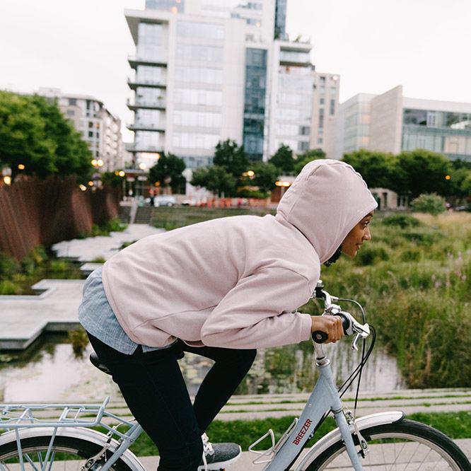 A woman riding a bike through an urban park.
