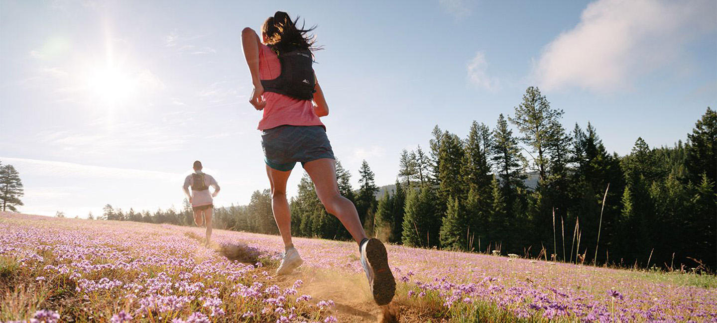 A man and woman in Columbia Montrail gear running through a flowery meadow.