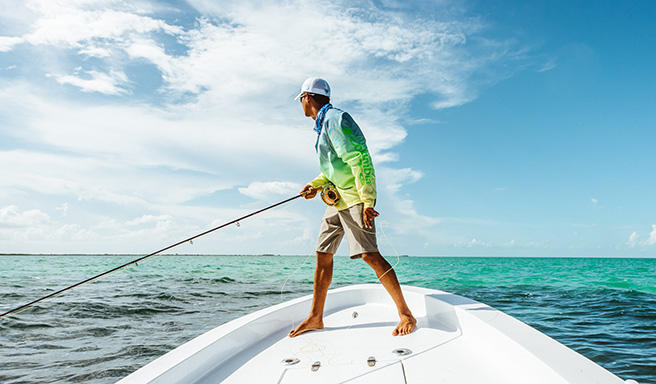 A fisherman in PFG gear stands up in the bow of a boat.