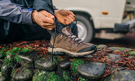 A man lacing up a hiking shoe with TechLite cushioning.